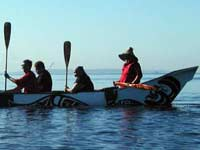 Native Americans paddling canoe
