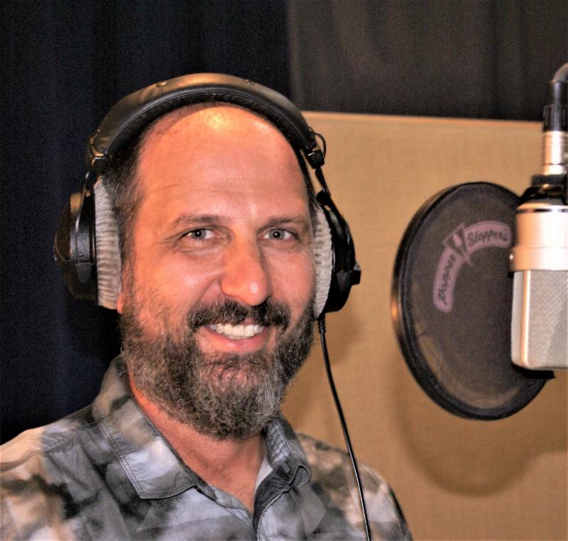 man at mic wearing headphones