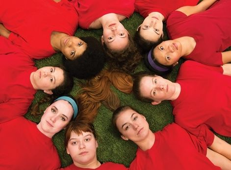 teenaged girls in soccer uniforms lying in a circle