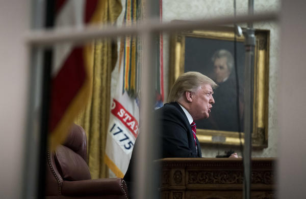 view through window of Trump in Oval Office