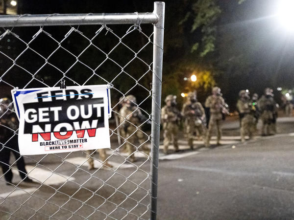 Sign reading FEDS GET OUT NOW with camoflage wearing officers in background