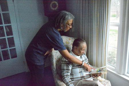 woman standing beside seated elderly man