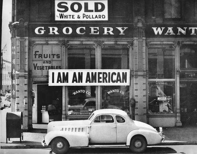 sign in store window reads I am an American