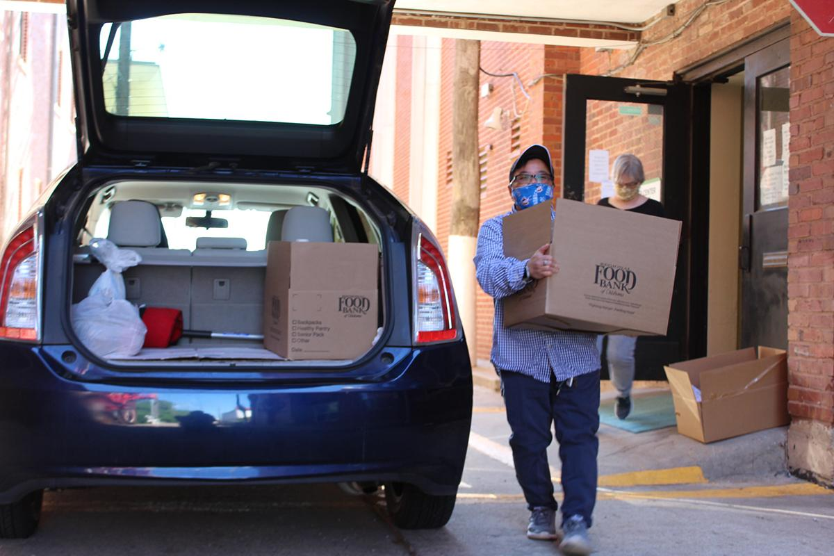 Masked man carries box of food to car