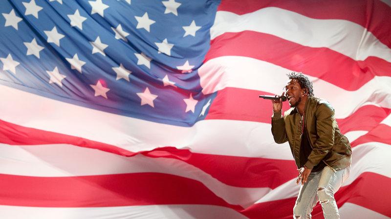 man sings in front of flag