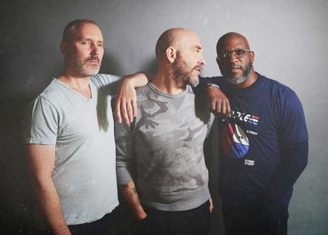 three men standing with arms around shoulders