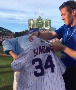 Scott putting on baseball jersey