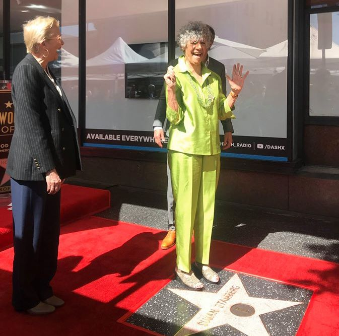happy woman standing on Hollywood star