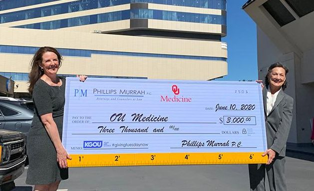giant ceremonial check held by two women