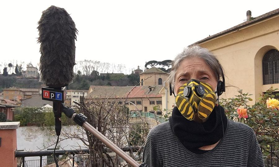 woman wearing mask holding microphone
