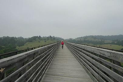 lone bicyclist on wooden bridge