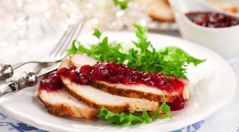 slices of turkey on a plate with cranberries
