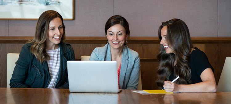 Three women working together at a computer