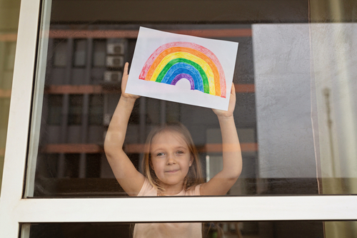 Kid painting rainbow during Covid-19 quarantine at home. Girl near window. Stay at home Social media campaign for coronavirus prevention_ let s all be well_ hope during coronavirus pandemic concept