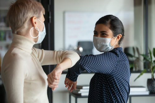 Smiling diverse female colleagues wearing protective face masks greeting bumping elbows at workplace_ woman coworkers in facial covers protect from COVID-19 coronavirus in office_ healthcare concept