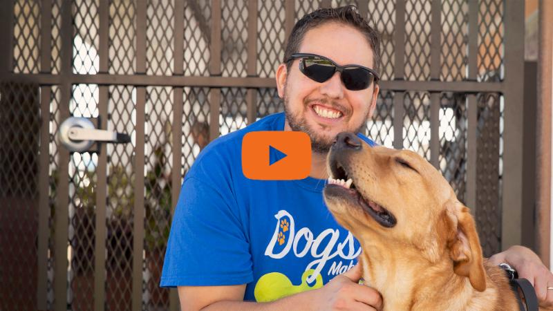 A man smiles while petting a smiling yellow lab. The photo links to a video story about this team.