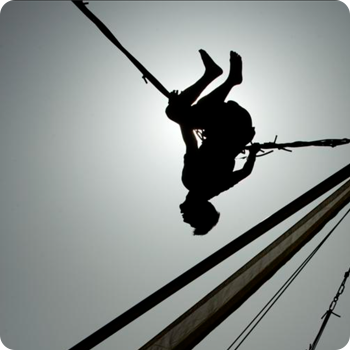 silhouette of person flipping on bungee cords