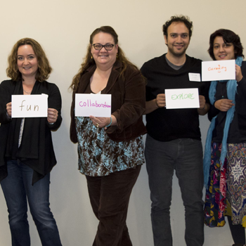 Faculty holding handwritten signs that read Fun Collaboration Explore Curiosity