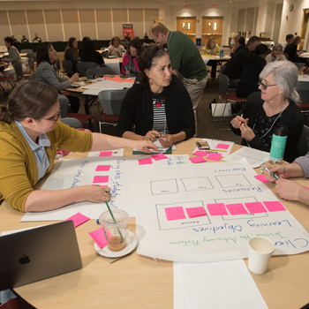 Three female attendees discuss over a large paper with post-it notes on it