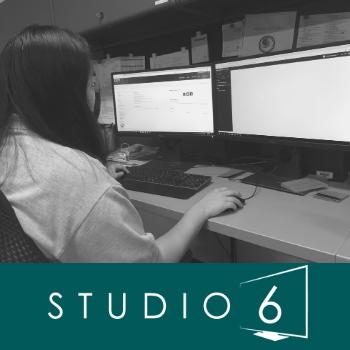 Studio 6 worker at a desktop.
