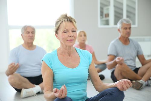 Group of senior people doing yoga exercises