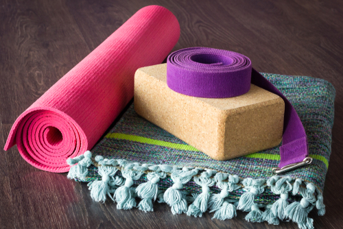 Yoga studio props selection on wooden floor. Pink mat_ cork brick_ purple belt and colorful cotton mat
