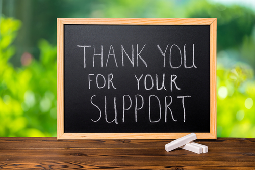 handwriting text thank you for your support is written in chalkboard on green light background and rustic wooden board_ close up