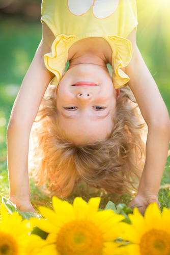 Happy child playing upside down in spring park