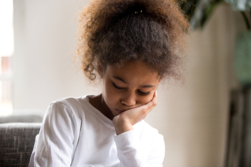 Sad little African American preschool kid feel down or depressed suffer from family problems_ upset small mixed race girl child sit alone at home_ bored or hurt_ offended having troubles with friends