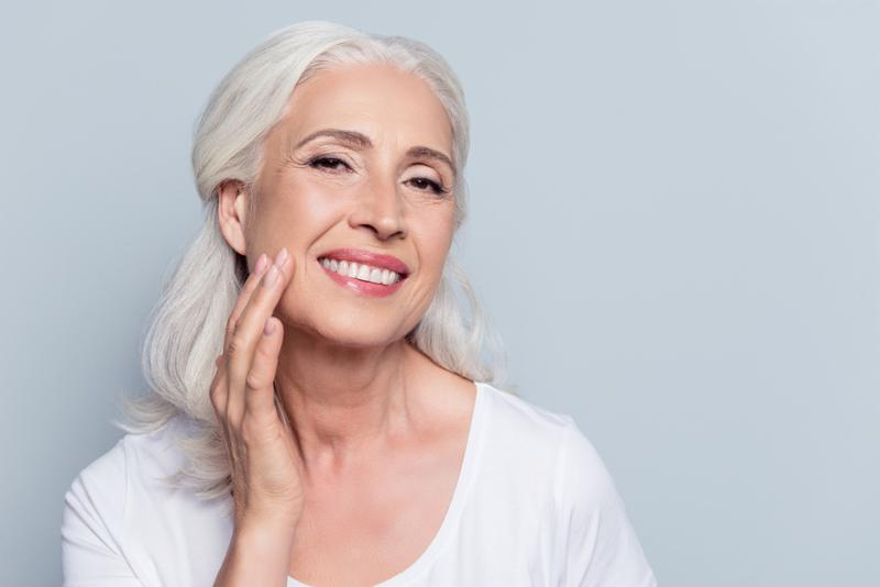 Charming_ pretty_ old woman touching her perfect soft face skin with fingers_ smiling at camera over gray background_ using day_ night face cream_ cosmetology procedures