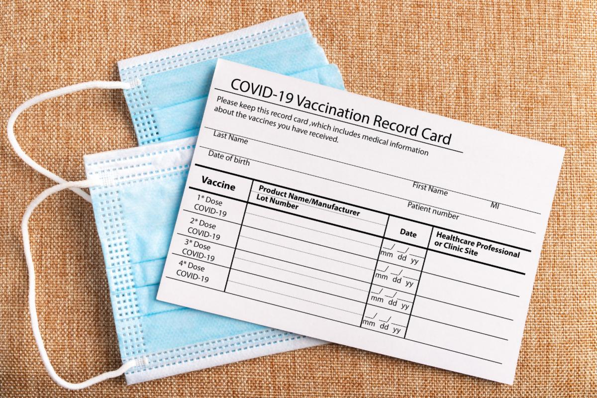 blue face mask behind blank vaccination record card