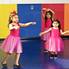 Four smiling Readiness students dressed in pink leotards and tutus practice ballet.