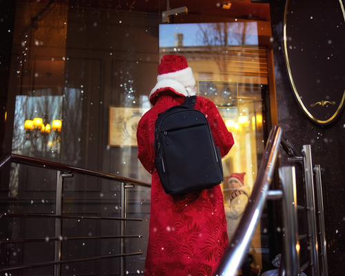 Santa Claus holds a bag with gifts and knocks on you on a dark background with snow