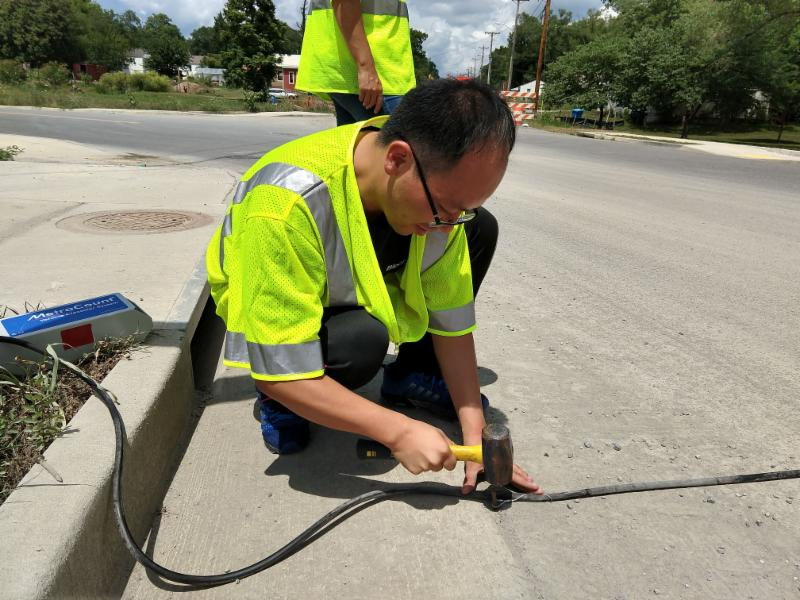 Photo: Virginia Tech researcher Tianjun Lu helps install the pneumatic tubes that detect bicycles.