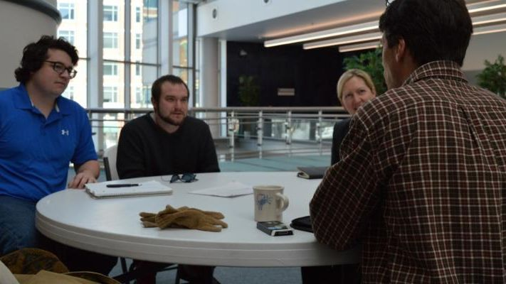 Four people converse at a table