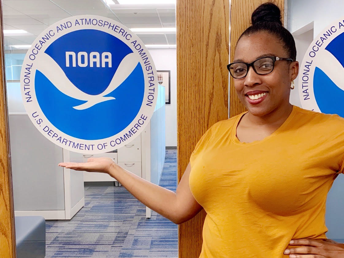 Shadaesha Green stands by a door with the NOAA logo
