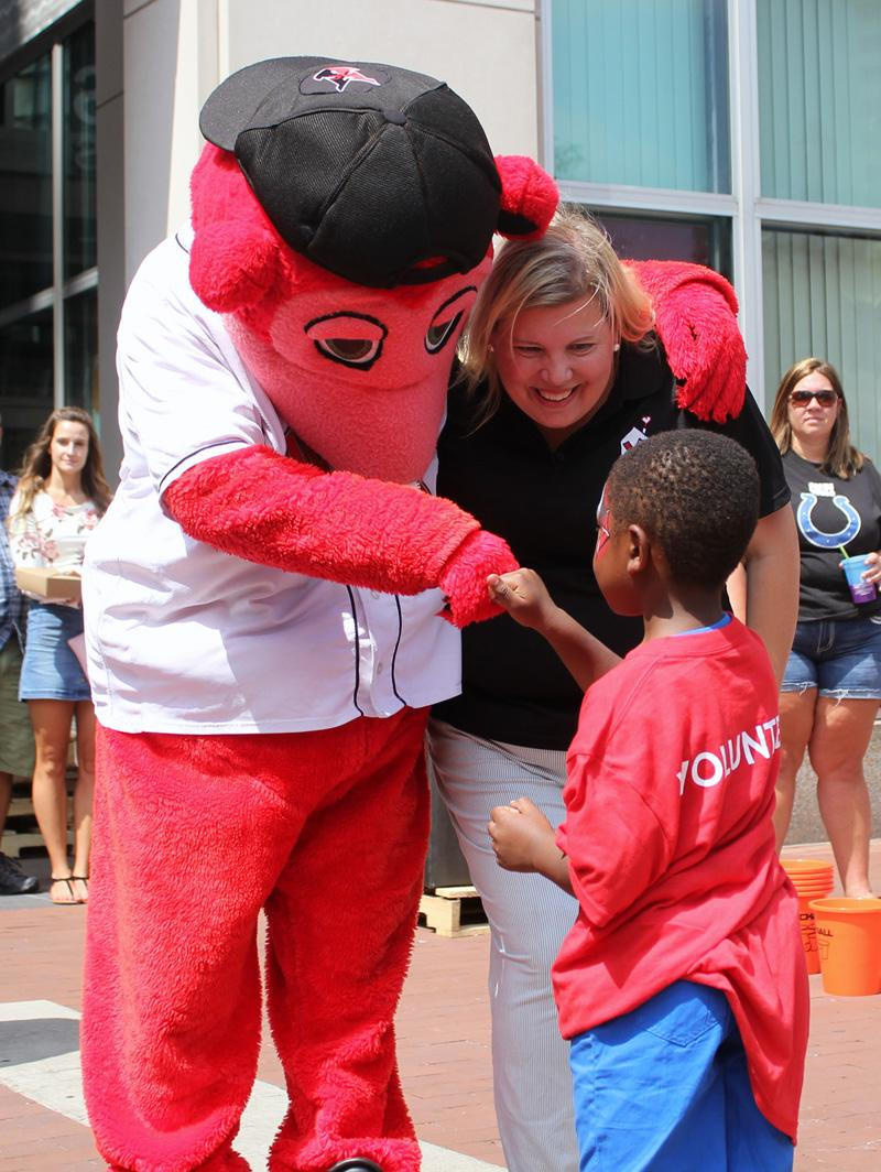Indianapolis indians mascot and ceo smiling and giving a knuckle touch to a kid