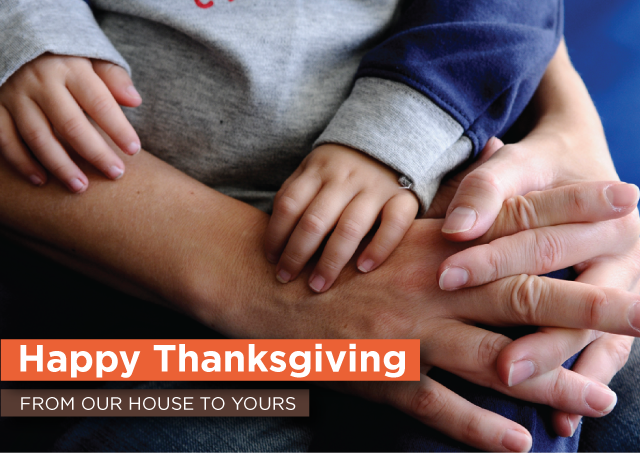 "close up of child sitting on adult's lap with only hands showing; text graphic overlay that reads ""Happy Thanksgiving from our House to Yours"""