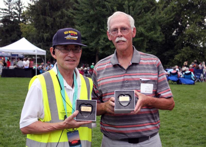 Two elderly men holding awards and smiling