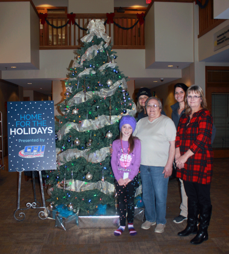 "Members of CFH Enterprises standing by their ""Home for the Holidays"" tree"