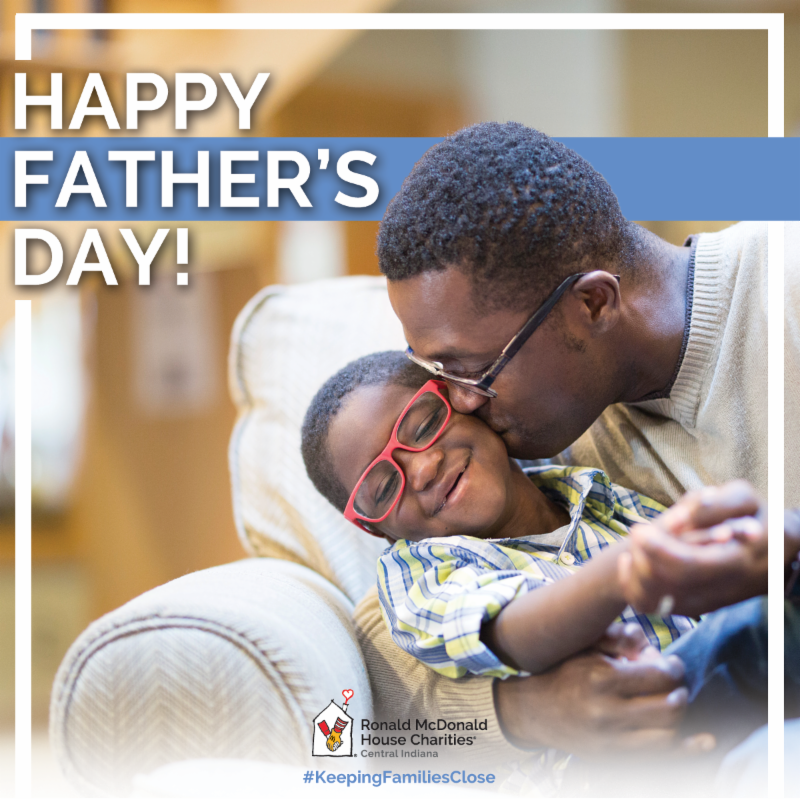 Father_s Day Graphic_ Black father kissing black son while sitting on couch