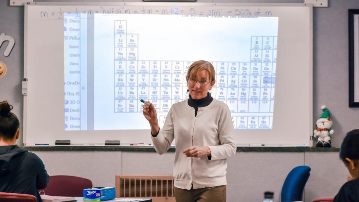 Teacher Liz in front of the periodic table, as class studies chemistry, to get ready for nursing school.