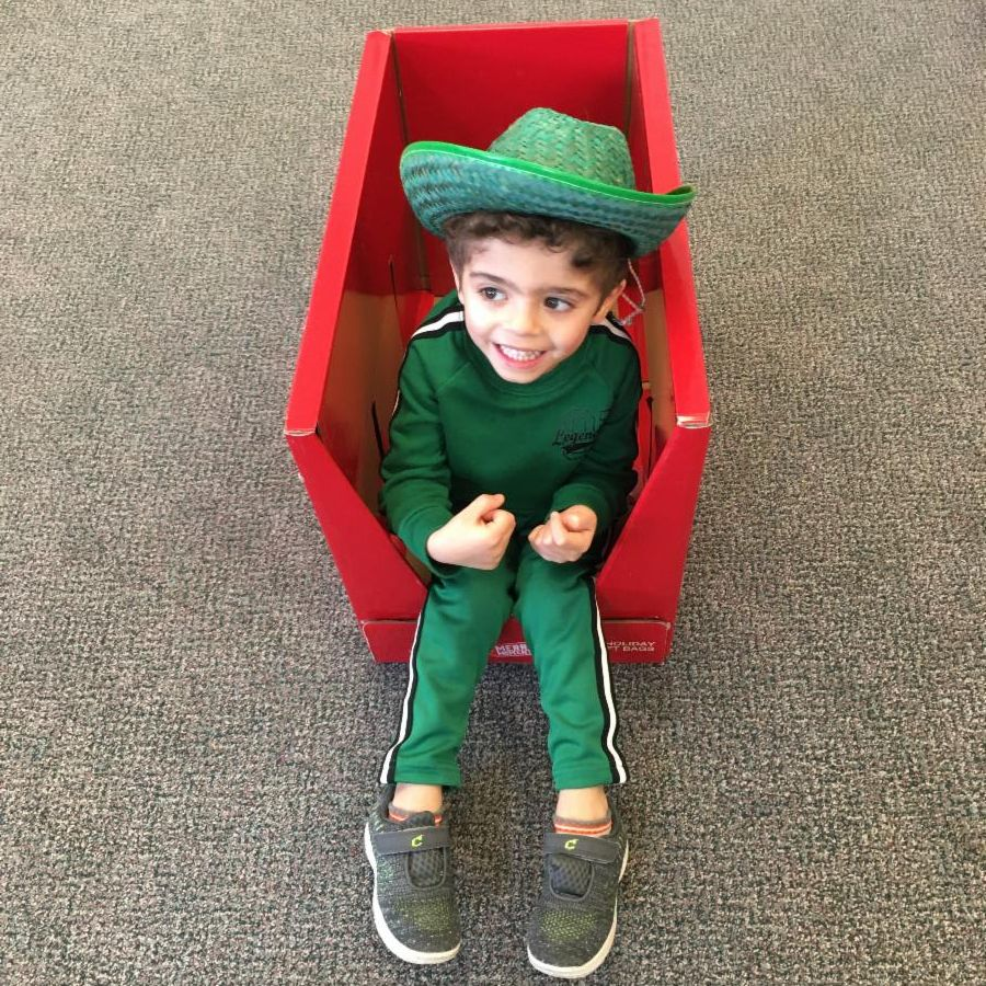 A little boy dressed up in all green with a cowboy hat on.