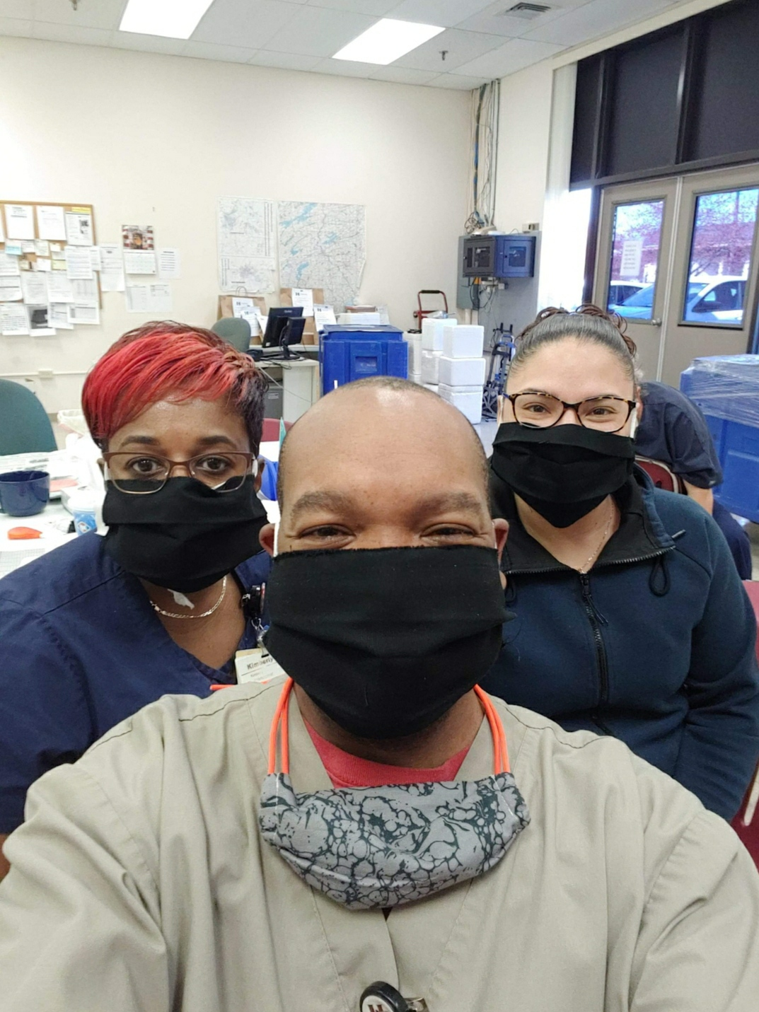 Three individuals who are wearing the mask that Mirta made.