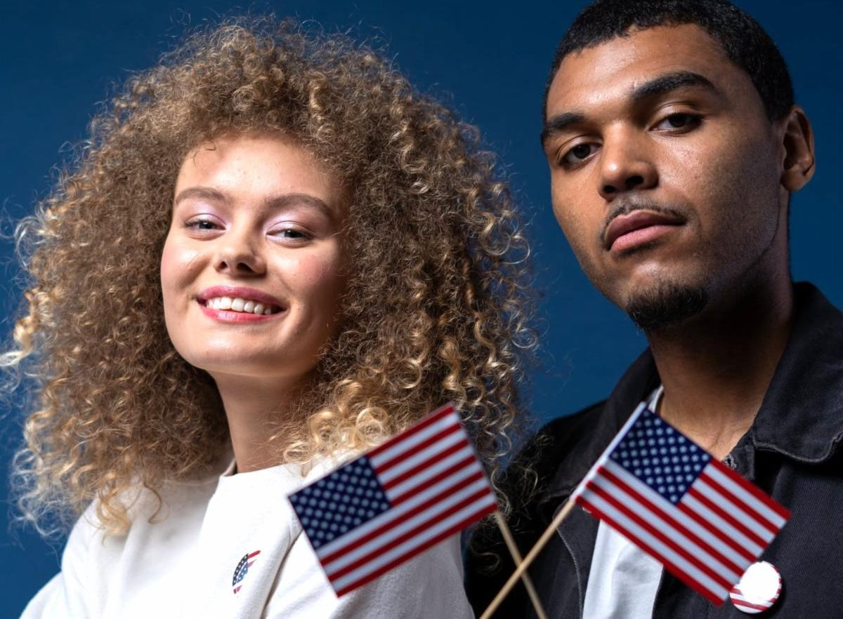 man and woman holding American flag