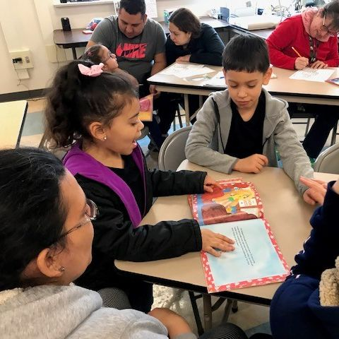 Parents reading to their kids in a classroom