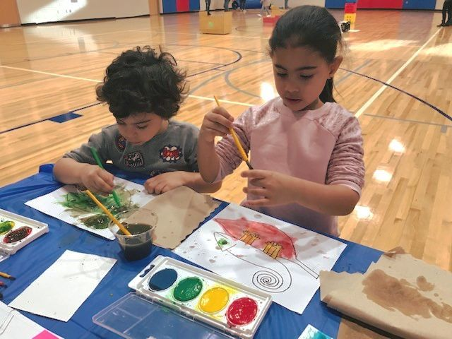 Two children are painting a Tangled color page during the family literacy family day.