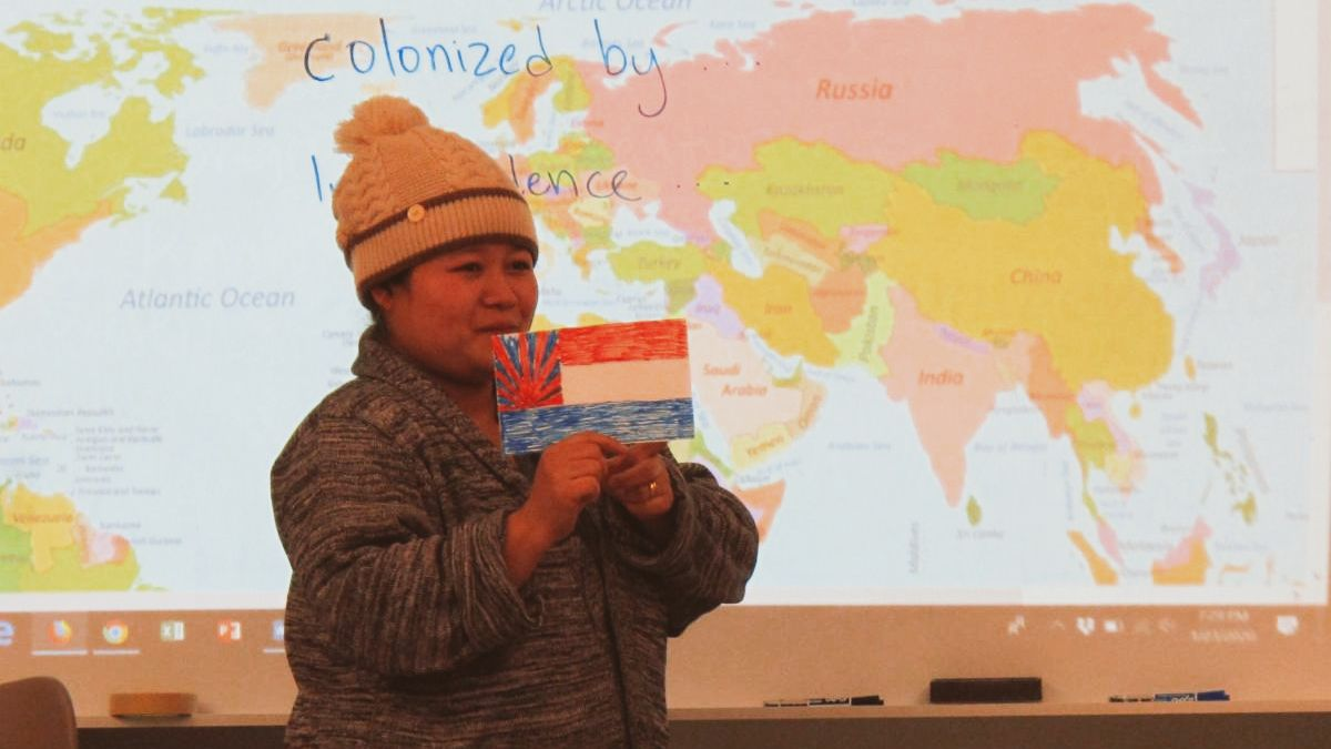 Student for citizenship class in front of world map sharing about her country while holding a flag that she created.