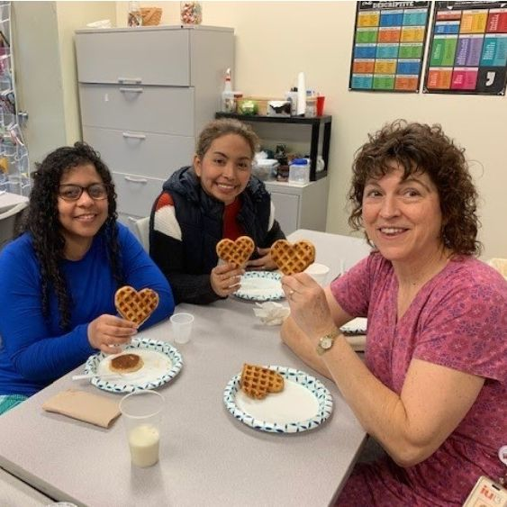 Students and teacher holding up heart-shaped waffles