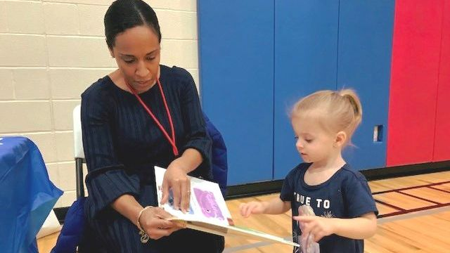A parent is reading a book to a child during the family literacy family day.